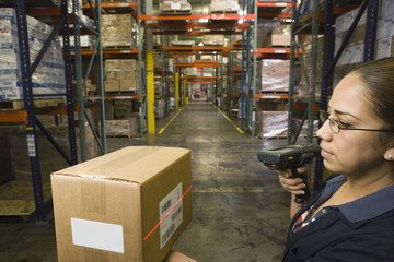 Hispanic woman scanning box in warehouse