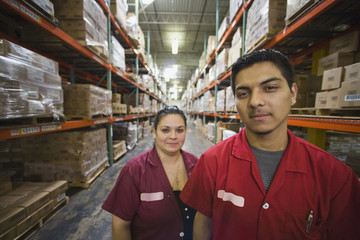 Hispanic workers smiling in warehouse