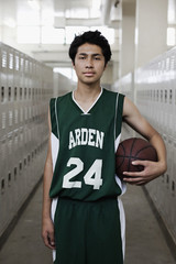 Serious mixed race basketball player holding ball in locker room