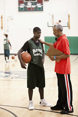 African coach talking with basketball player in gym