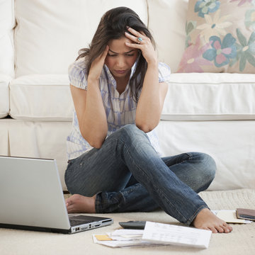 Hispanic woman looking at bills with head in hands