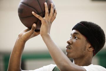 African basketball player shooting basketball in gym