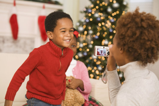 African mother taking picture of son at Christmas