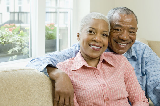 African couple hugging in living room