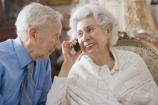 Senior Hispanic couple using cell phone