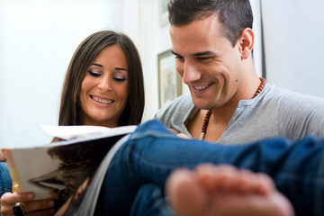 couple sitting on couch and reading a magazine
