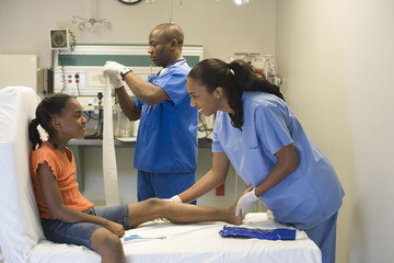 Doctor and nurse helping girl with injured leg