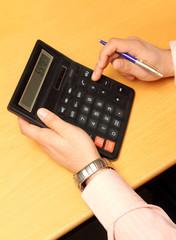 businessman counts money on calculator