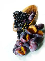 Pflaumen mit roten Weintrauben in Holzschale