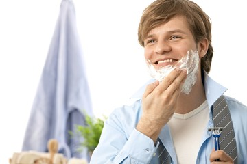 Young man shaving in the morning