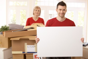 Smiling couple surrounded with boxes in new house