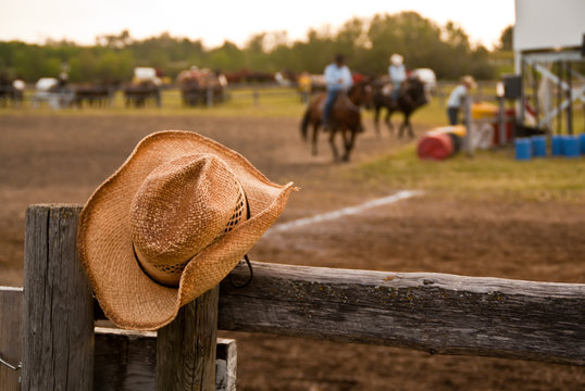 Cowboy hat hung on the fence at a rodeo with horses and riders