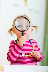 Toddler girl playing with magnifier