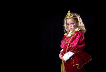 Adorable little girl in a princess costume on a black background
