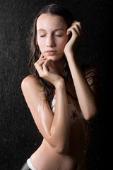 portrait of pretty girl with close eyes in water studio