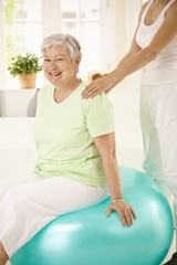 Personal trainer assisting senior woman