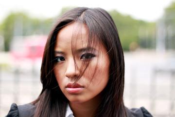 Thoughtful young beautiful asian businesswoman. Windy.