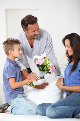 Father and child giving flowers to woman