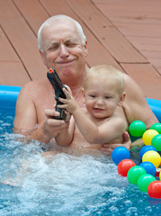 Grandfather and grandson having fun in the pool.