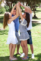 Group of happy friends with raised arms