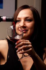 Donna che versa il vino rosso nel calice
