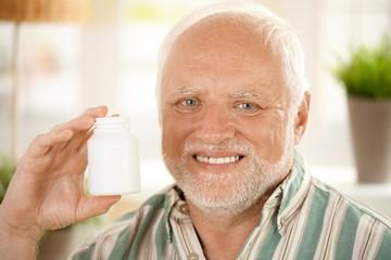 Happy senior man holding medication