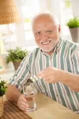 Portrait of senior man taking medicine at home