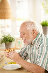 Older man eating pizza slice at home