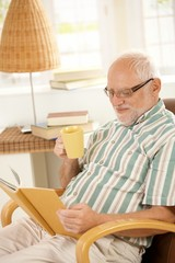 Elderly man reading book and having tea.