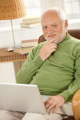 Portrait of senior man with laptop computer