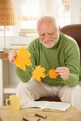Senior man holding autumn leaves
