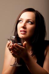 Donna pensierosa con calice di vino rosso