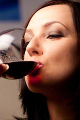 Donna che beve una calice di vino rosso