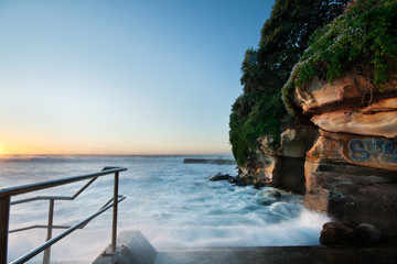 rocky coastal view with rushing wave and handrail beside