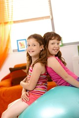 Young girls sitting on exercise ball