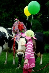 Girl patting decorated cow