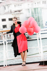 attractive young woman with red balloons on urban background
