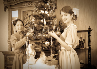 Vintage photo of  daughter with mother decorating Christmas tree