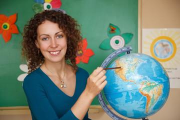 Portrait of schoolteacher in school. showing on globe