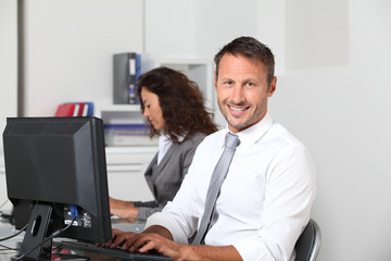 Smiling businessman working on computer
