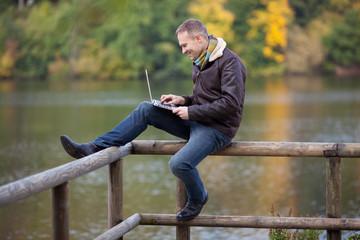 mann mit laptop am see