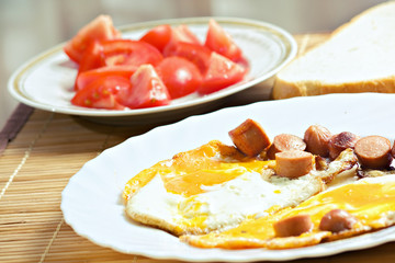 Breakfast with eggs, sausage, bread and tomato