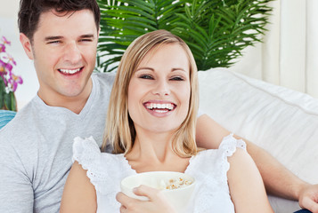 laughing couple eating pop-corn lying on the sofa in the living-
