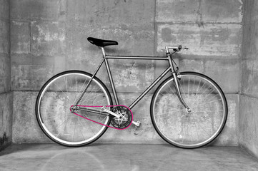 A fixed-gear bicycle in black and white with a pink chain
