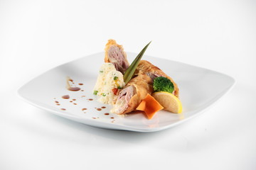 Meat rolls served with vegeables on a white plate