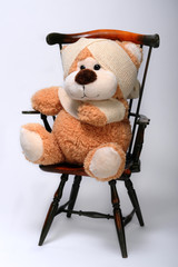 Injured teddy bear sitting in chair.