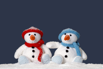 two cute snowmen sitting in the snow