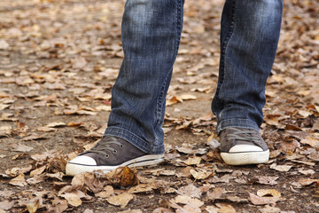 closeup of woman's legs in jeans and sneakers, outdoor in autumn
