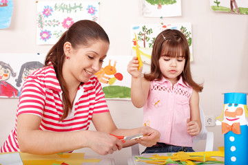 Child with scissors cut paper in play room.