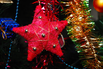 Red star hanging on fir tree